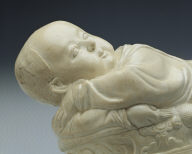 Pillow in the shape of a recumbent child with white glaze
