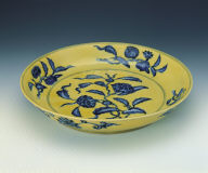 A yellow ground saucer with blue floral motif